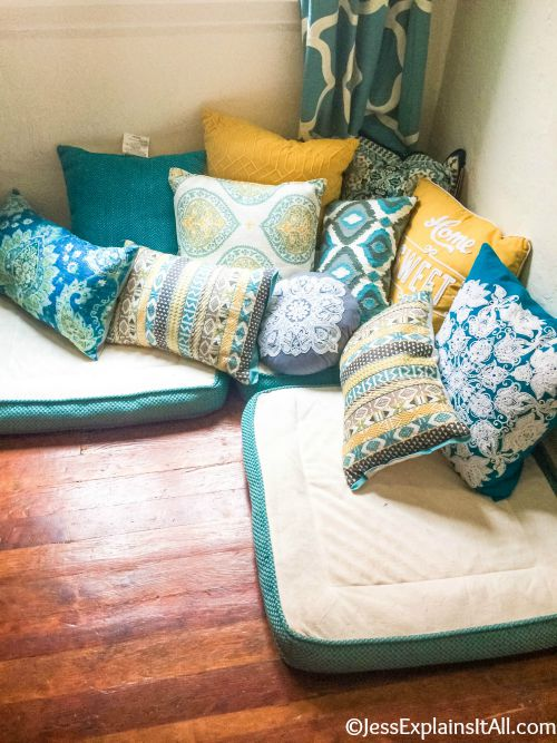 A sunny corner of a room with meditation pillows set up on the floor.