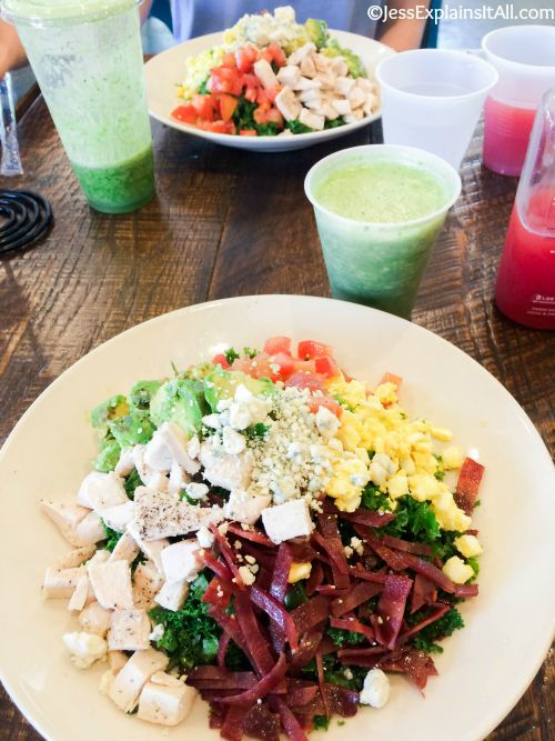 Two vegan cobb salads, green juice and pink smoothie on a wooden table.