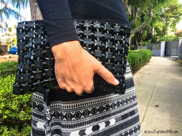 A black vintage clutch in front of a black and white patterned skirt.