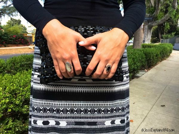 A closeup of a woman holding a black clutch with vintage rings.