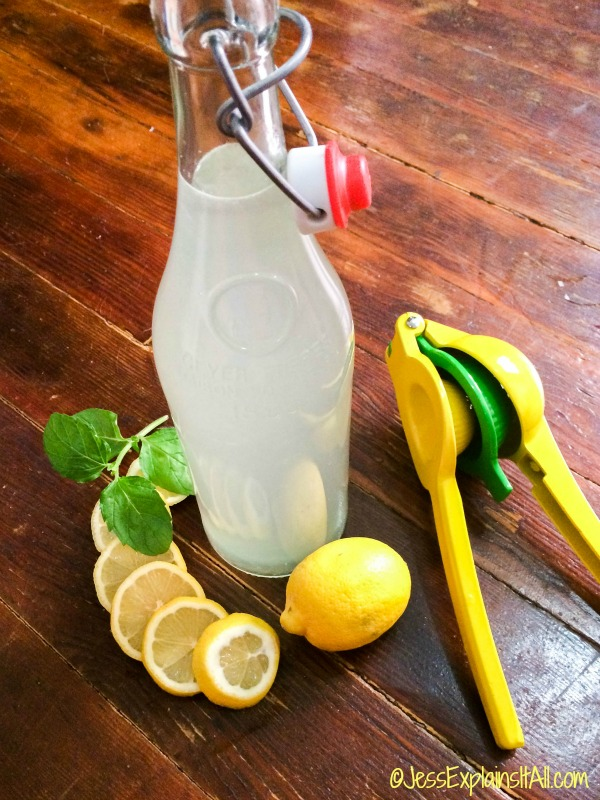 bottle of homemade lemonade with juicer and lemons