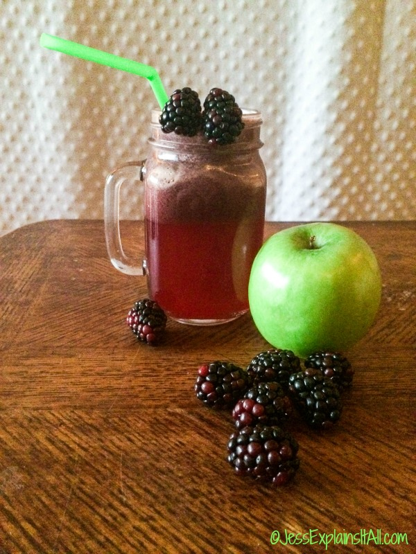 A mason jar mug filled with juice on a table next to blackberries and a green apple.