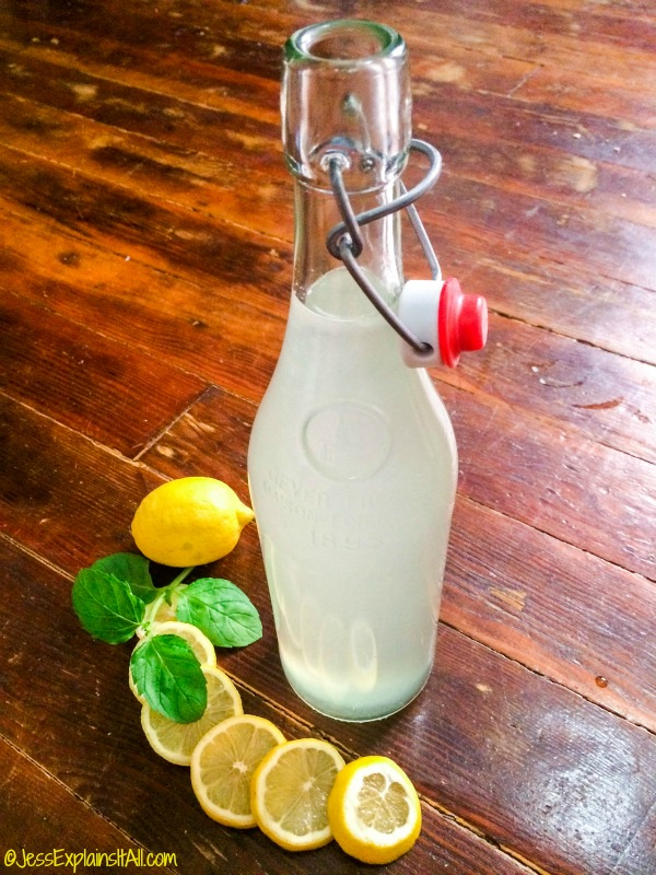 A large bottle of homemade lemonade on a wooden surface next to lemons.