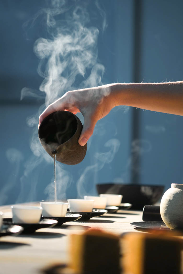 A tea ceremony. Hot water being poured into tea cups.