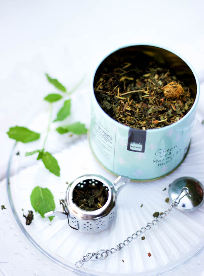 A tin of loose leaf tea and a tea infuser.