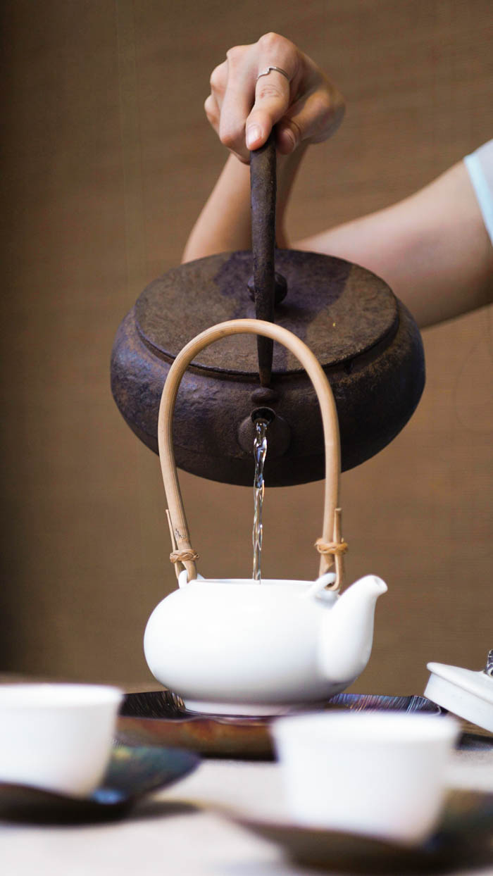 Pouring hot water for tea from a tea kettle into a teapot.