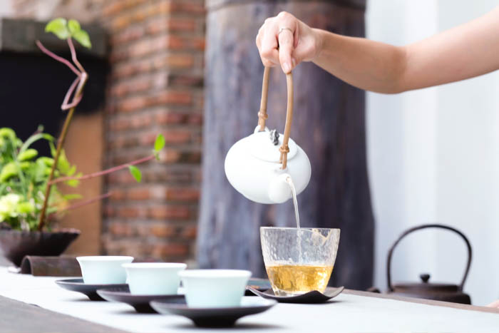 Steeped tea being poured into four teacups.