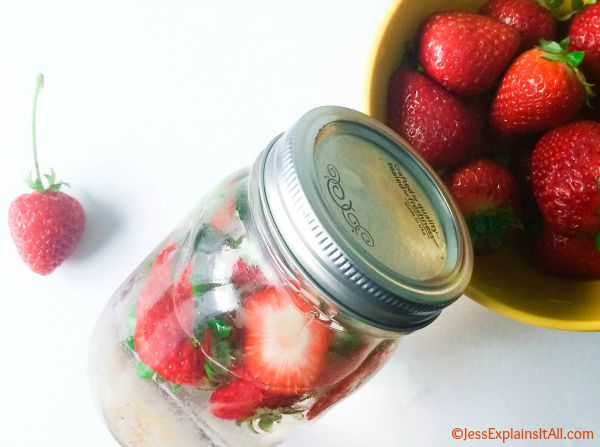 A mason jar filled with strawberry water, next to a bowl of strawberries.