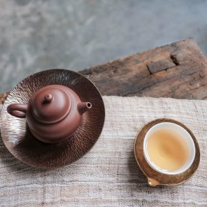 A zen photo of a teapot and cup of tea.