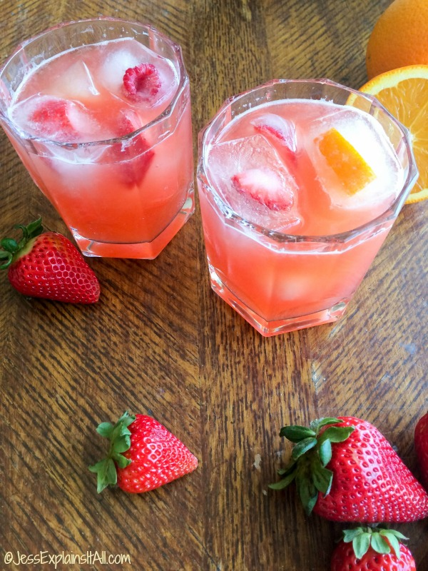 Tropical mocktails with fruit ice cubes on a table with strawberries.