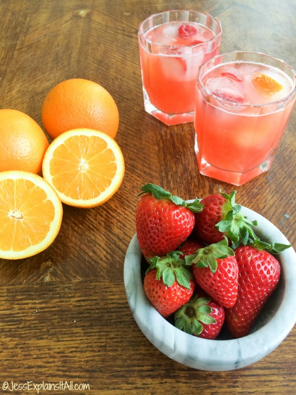 Two glasses of low calorie tropical mocktails on a table next to oranges and strawberries.