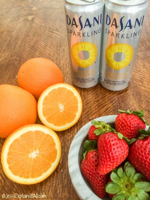 Two cans of Dasani Sparkling Pineapple water next to oranges and strawberries.