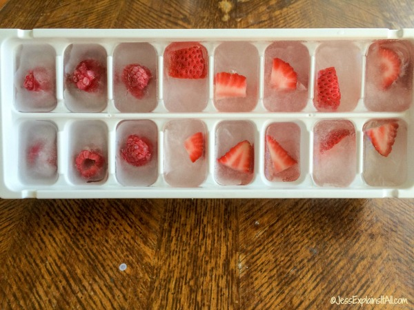 A tray of raspberry and strawberry fruit ice cubes.