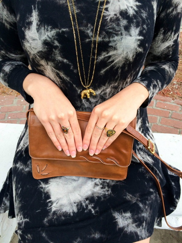 A detail shot of the purse on a woman's lap and her hands.