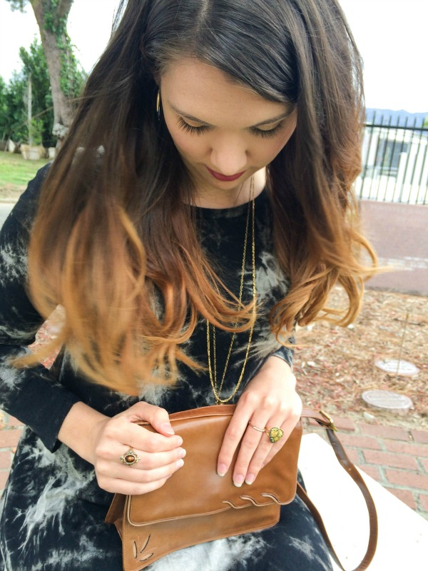 A brunette girl looking down at the purse on her lap.