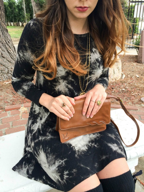 A girl sitting on a bench wearing a black tie dye dress.