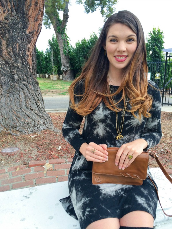 A girl on a bench holding a brown leather purse.