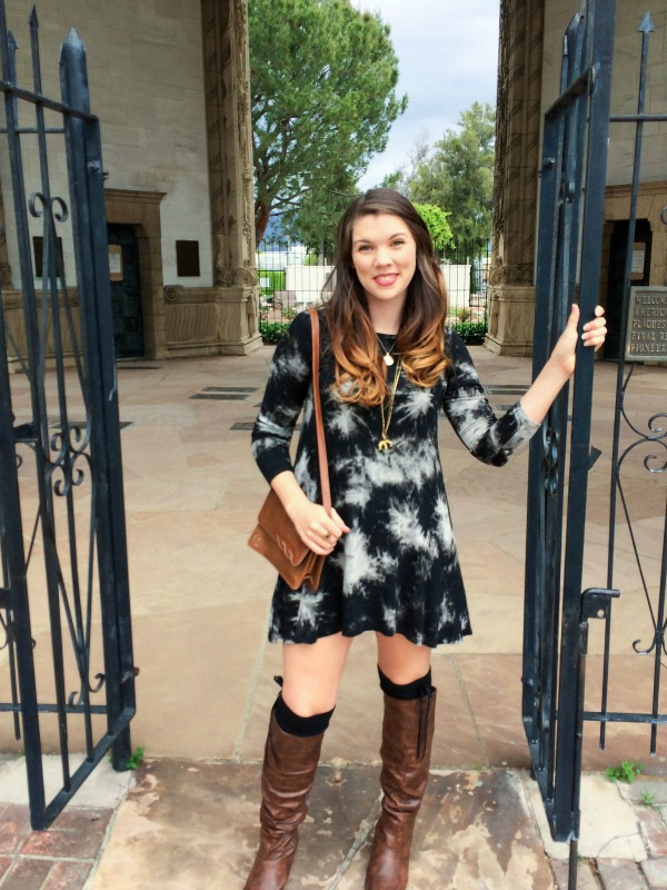 Girl in a black and white dress standing in a gate's entryway.