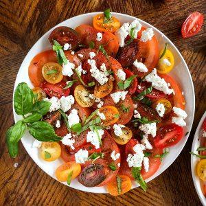 Tomato mozzarella salad plate garnished with basil and balsamic
