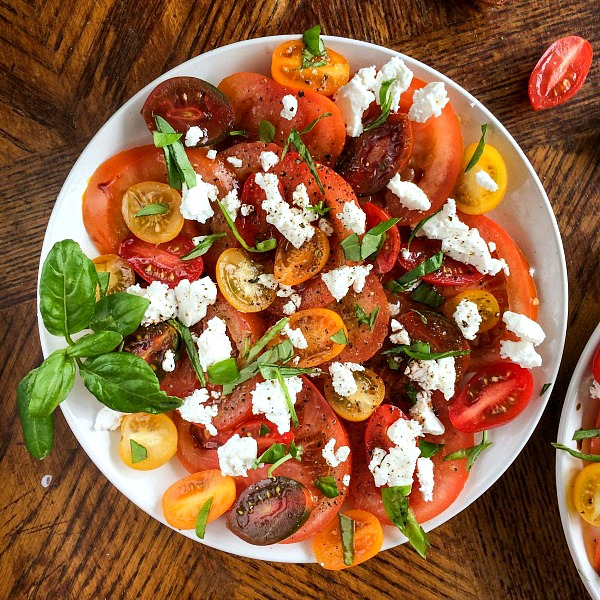 Tomato mozzarella salad plate garnished with basil and balsamic