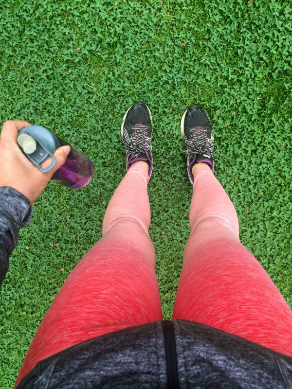 A photo of pink leggings, tennis shoes and a purple water bottle from above.