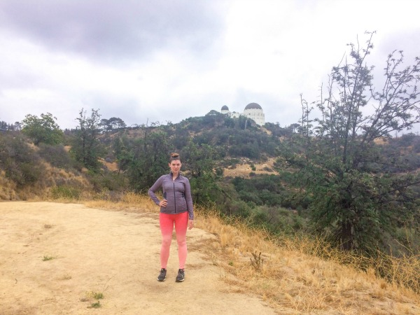A girl standing on a hiking trail in front of the Griffith Observatory.