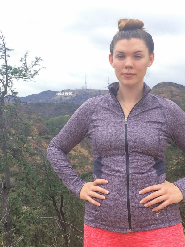 A girl standing on a mountain in workout clothes.