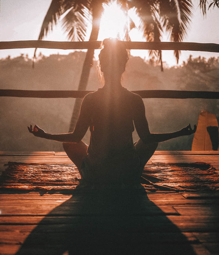 A woman meditating at sunrise outside in front of a palm tree.