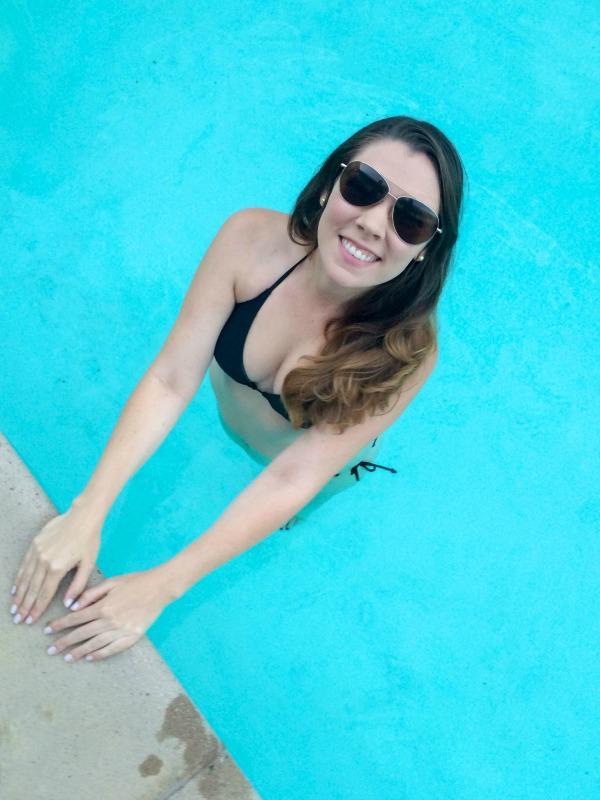Brunette wearing a black bikini and sunglasses in a pool.
