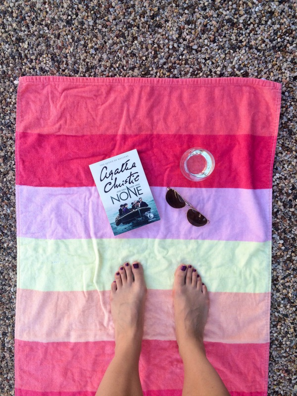 A beach towel with a book, sunglasses, wine and painted toes.