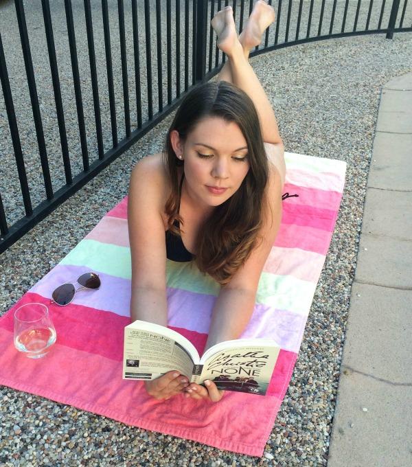 Brunette girl reading an Agatha Christie book on a beach towel.