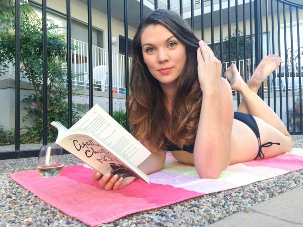 A brunette poolside reading a book.