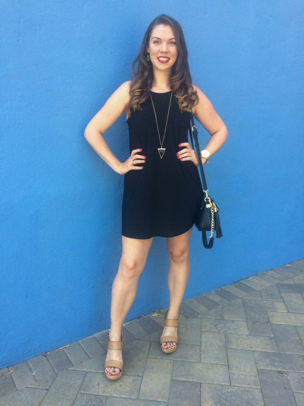 girl in a black dress against a blue wall