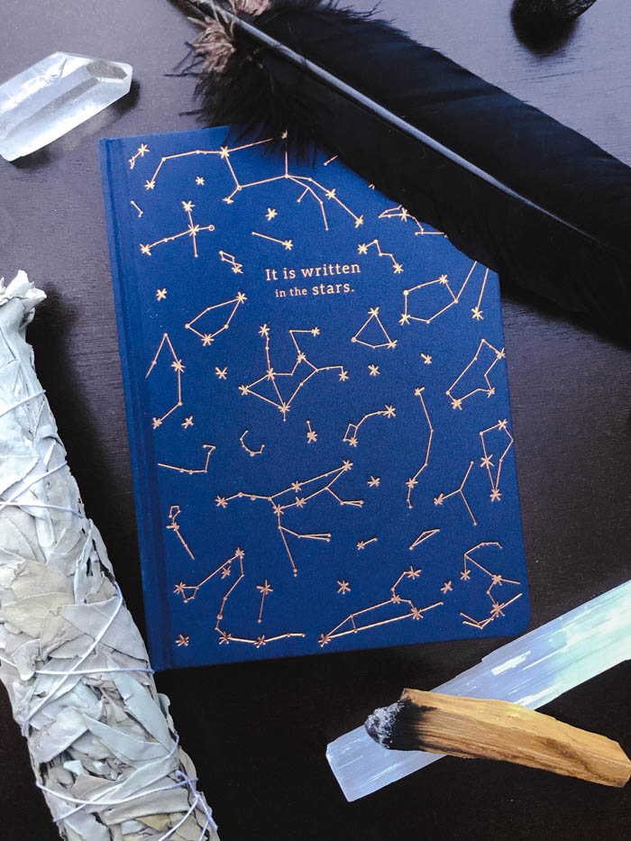 An assortment of smudging items arranged around a notebook with constellations on it.