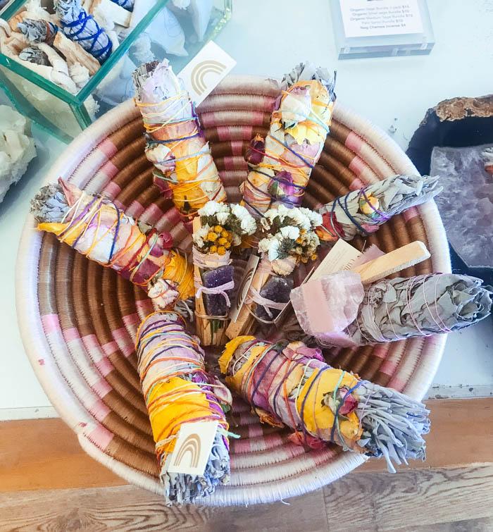 A smudging basket holding floral smudge sticks. Some of the bundles have crystals attached.