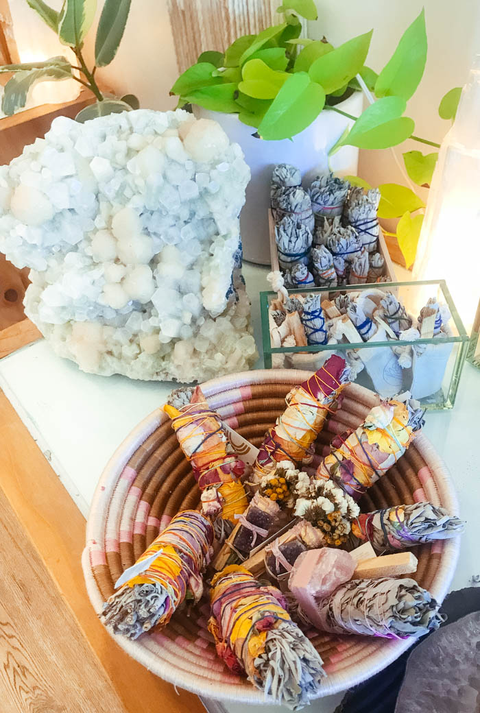 A table holding a smudging basket of smudge sticks, a crystal and a box of white sage bundles.