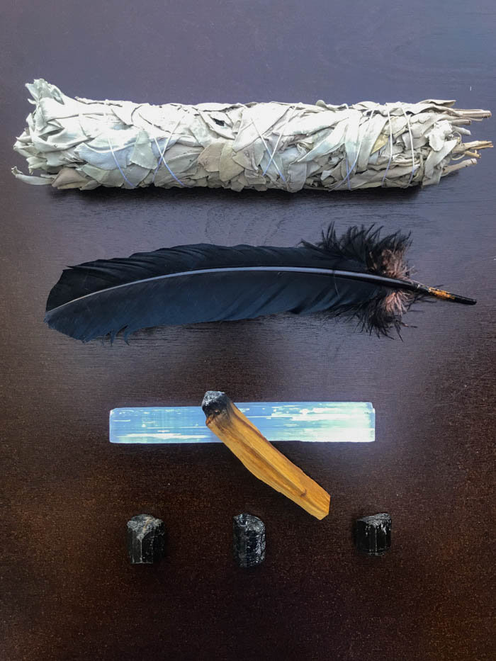 A smudge stick, smudging feather, palo santo stick, selenite and black tourmaline on a table.