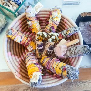 A smudging basket of white sage smudge sticks, floral smudge sticks and palo santo.
