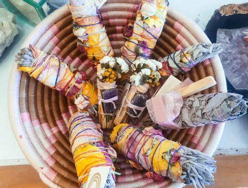 A smudging basket of white sage smudge sticks, floral smudge sticks and palo santo.
