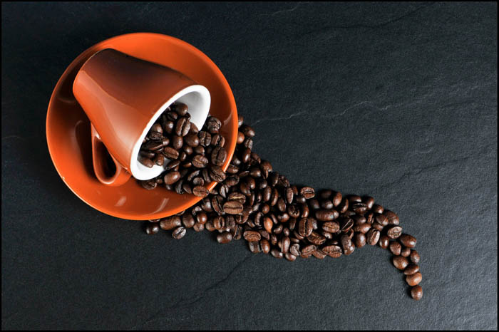 An orange coffee cup with coffee beans in it.