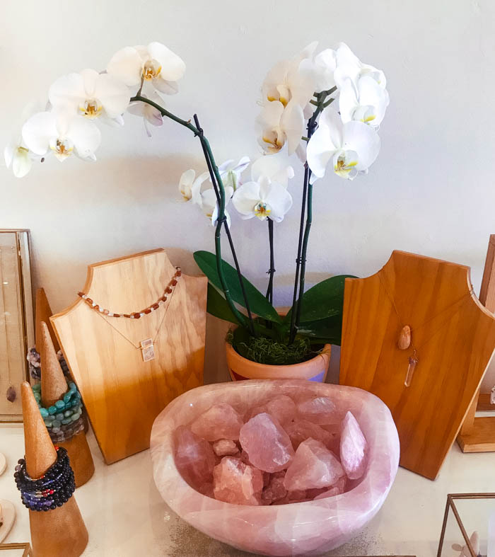 Raw rose quartz in a rose quartz bowl, placed in front of an orchid.