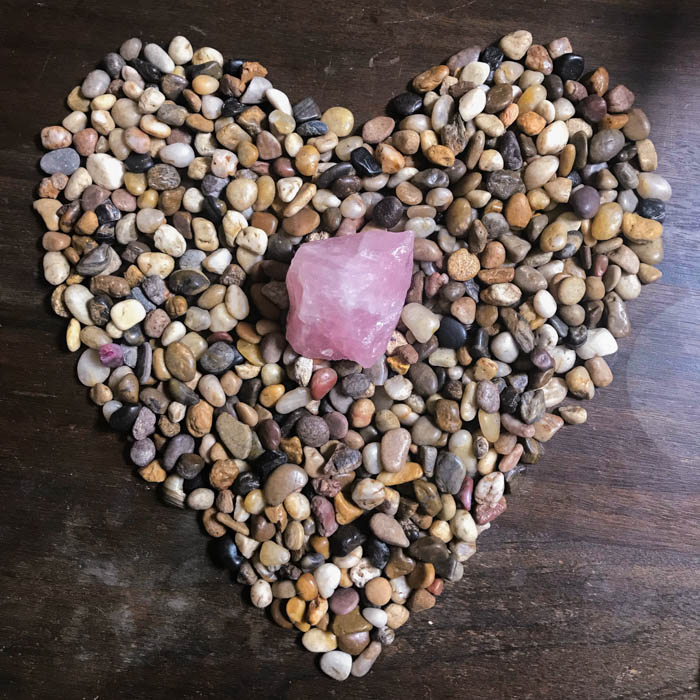 Raw rose quarts on a formation of stones in a heart shape.