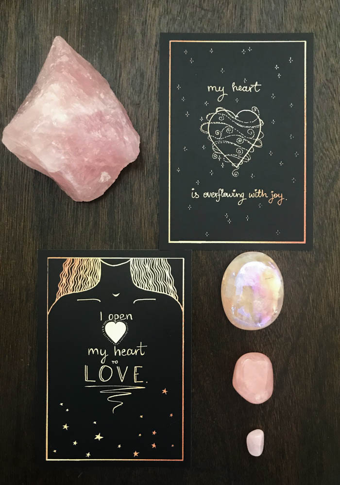 Rose Quartz next to affirmation cards with loving messages.