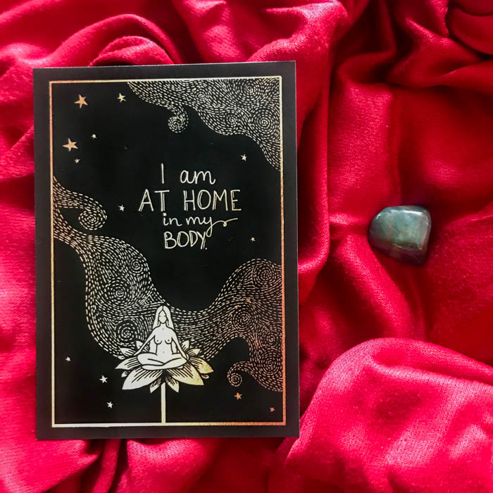 """A tumbled bloodstone and an affirmation card reading """"I am at home in my body""""."""