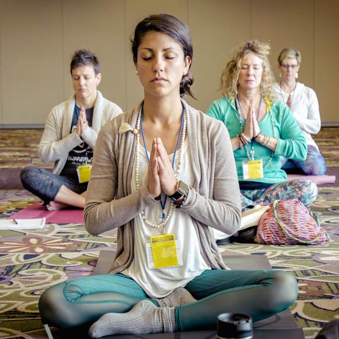 A group meditation at a yoga retreat, 4 women sitting crosslegged.