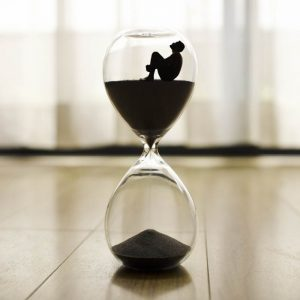 A person sitting in an hourglass meditating on the sands of time.