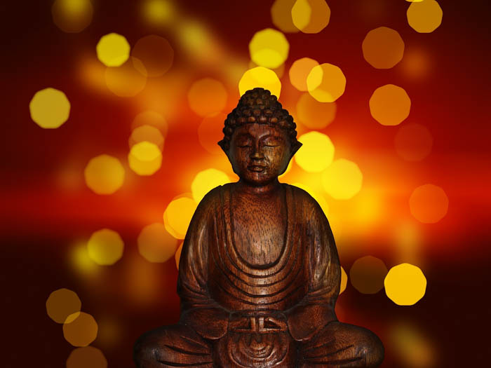 A Buddha meditation statue photographed with lights and bokeh in the background.