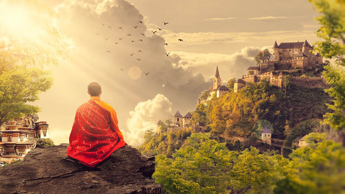 A Buddhist Monk sitting on a mountain with a view of the landscape.