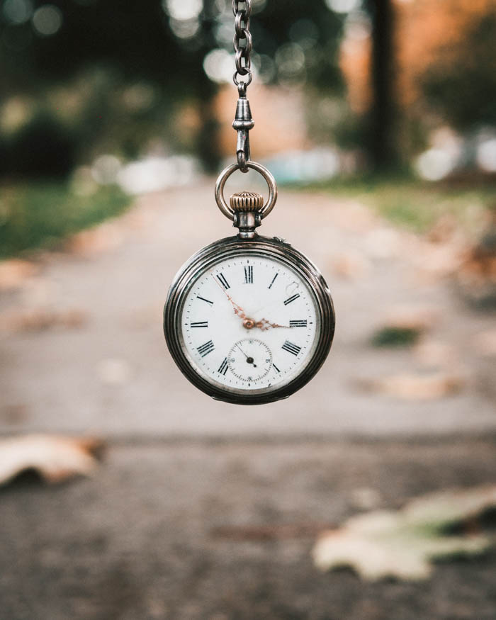 A vintage pocket watch in focus in a blurred out collegiate background.