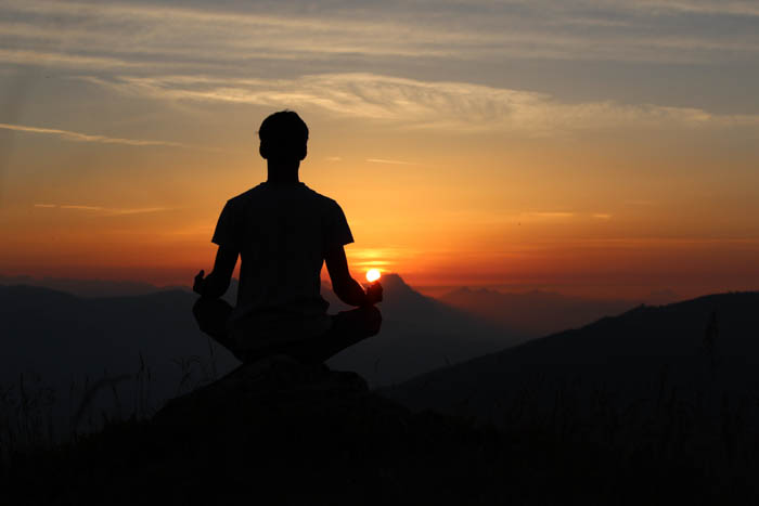 A man sitting on a mountain at sunset during meditation time.